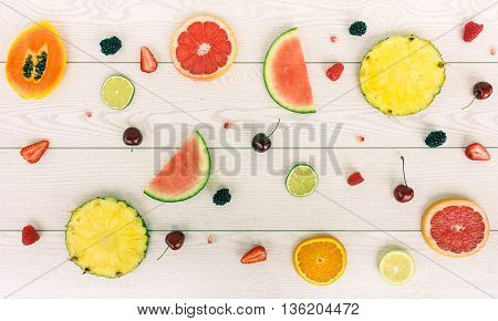 Minimal composition of tropical and european fruits - Mix of summer colored fruits on wood background - Healthy lifestyle concept - Soft saturated filter with main focus in the middle of the frame