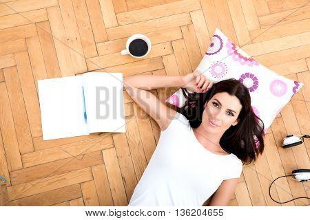 A beautiful young woman laying on the floor, with a smartphone, headphones and tablet pc next to her