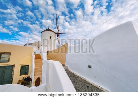 White windmill and picturesque cloudy sky in Oia or Ia on the island Santorini, Greece