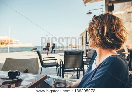 Young Woman Sitting In Coffee Bar And Looking At Old Port In Chania, Crete, Greece