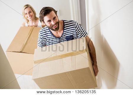 Couple holding a carton in their new house