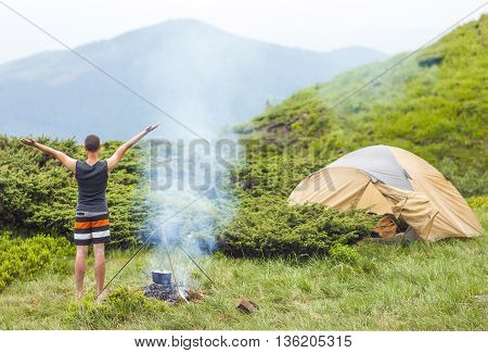 Hiker tourist standing with raised hands enjoing nature near camping fire with tent and mountain behind