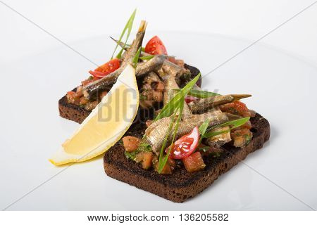 Italian sandwich. Bruschetta with fish on a white plate