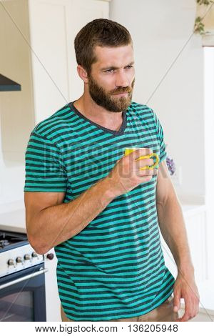 Thoughtful man having a coffee in kitchen at home