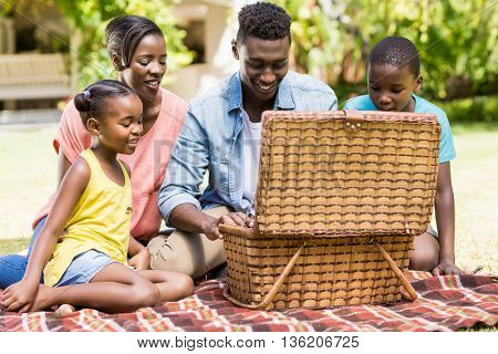 Happy family looking the wicker basket at park
