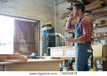 Carpenter calling someone in a dusty workshop