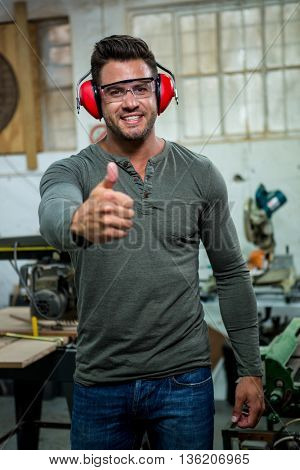 Carpenter is posing with thumbs up in a dusty workshop