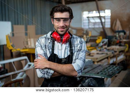 Carpenter is posing in a dusty workshop