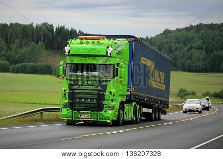 SALO, FINLAND - JUNE 26, 2016: Lime green Scania R series Semi trailer show truck moves uphill along road in South of Finland at Summer.