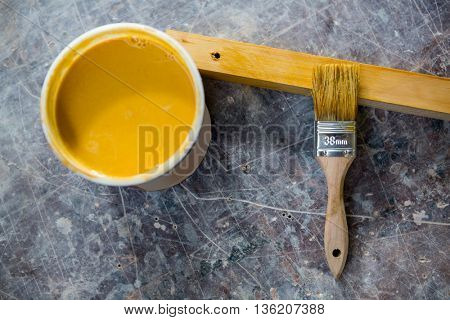 Image of tin of paint and paintbrush on a table