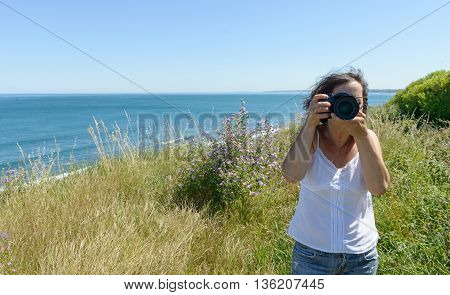 Happy woman on vacation photographing with a dslr camera to the sea