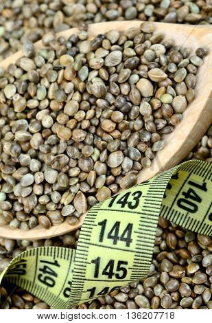 Hemp seeds in wooden spoon with centimeter