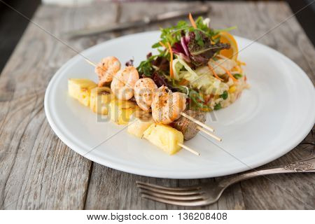 Grilled shrimps, pineapples skewer with rice and vegetables