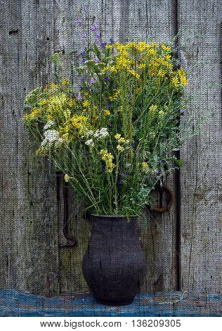 Wildflowers bouquet in a black clay pot on a wooden background - Photo made with canvas texture effect