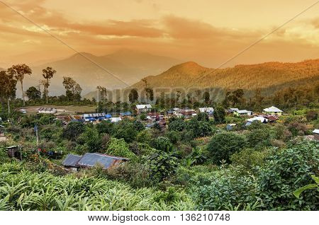 Beautiful view of Silerygaon Village with Kanchenjunga mountain range at the background at orange colored dusk light at Sikkim India