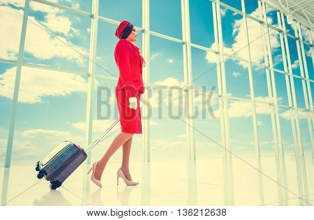 Young stewardess with suitcase in airport