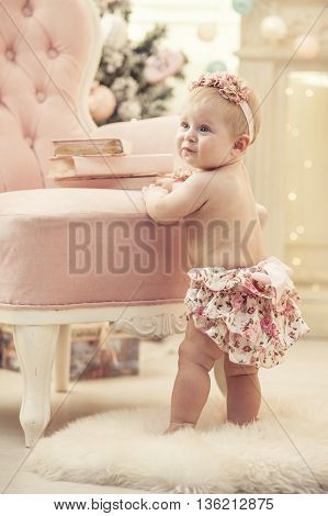 Kid Baby Girl In Pink Clothes And Happy Interior
