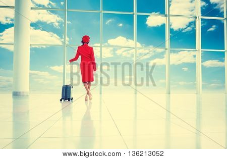 Young stewardess with suitcase