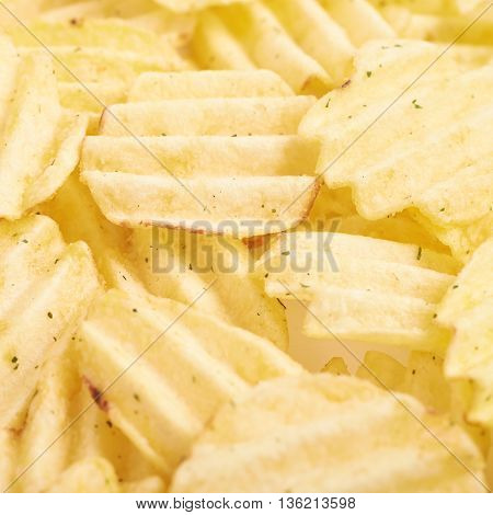 Surface covered with multiple seasoned potato chips crisps as a background composition