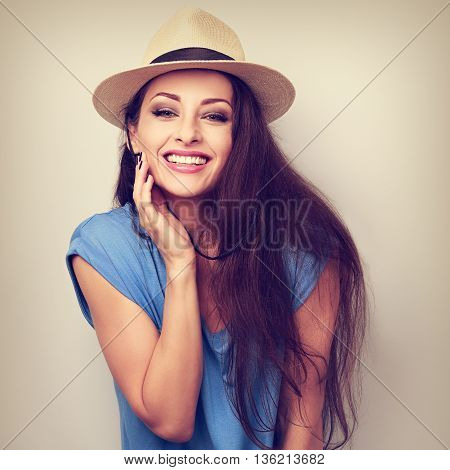 Natural emotional laughing woman in summer hat looking happy. Vintage toned portrait