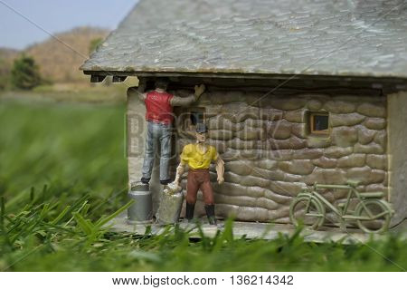 mini worker repair house in countryside and green field and mountain view on blur selective focus at repair man - can use to display or montage on product