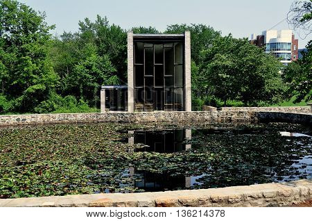 Waltham Massachusetts - July 12 2015: Berlin Jewish Chapel at Brandeis University with pond filled with lily pads and blossoms
