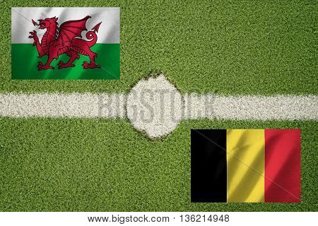 wales and belgium flag on football green field and haft line