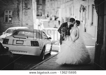 Kissing newlyweds background muscle car at wedding