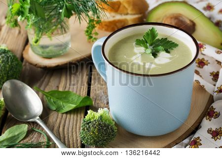 soup of broccoli and avocado keramtcheskoy blue cup on the old wooden table background.Selective focus.