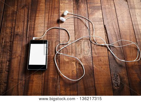 Black smartphone with a blank screen and headphones. Mobile phone with headphones on an old wooden table background.