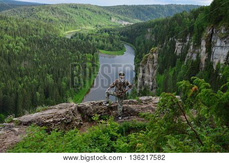 man with cowboy hat stands on top of the mountain.