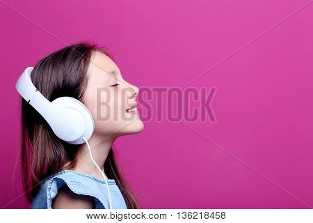 Portrait Of Young Girl With Headphones On Pink Background