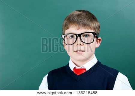 Young boy standing near the blackboard close up
