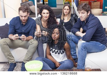 Group Of People Having Fun On The Couch Playing With The Joystic