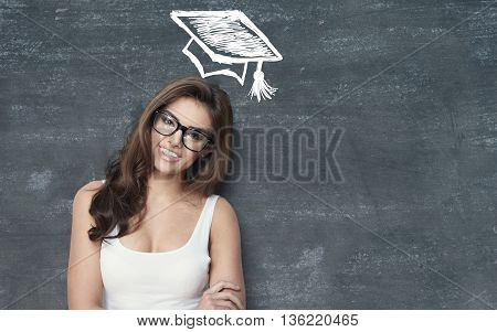 happy student girl standing infront of a chalkboard.