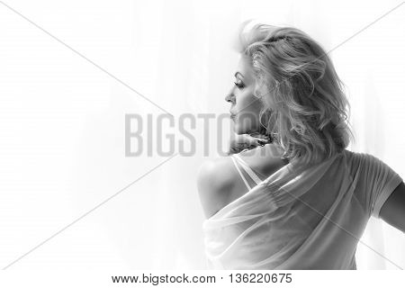 Portrait of adult blonde woman looking at window and thinking of something. Black and white photo.
