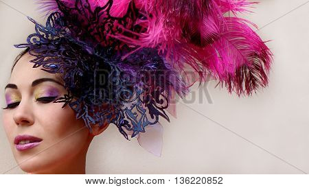 Close-up portrait of beautiful young woman in lace lilac purple hat fascinator with feathers on white background. Fashion professional violet purple shades make-up. Model shot.