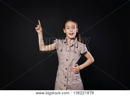 Small girl has an idea. Child shows finger up as an eureka, inspiration sign. Smart schoolgirl studio portrait at black background, school study and getting knowledge concept.