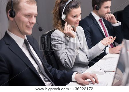 Focused telephone consultants talking with their clients and working on computers
