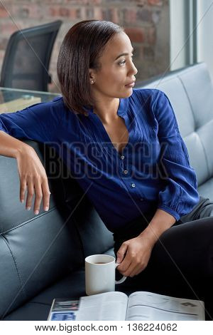 Casual portrait of businesswoman on couch having coffee, deep in thought