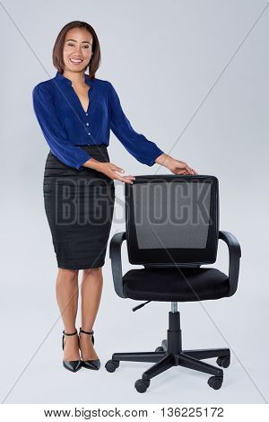 Pretty friendly hispanic indian asian woman showing a vacant office chair, recruitment hiring employment concept