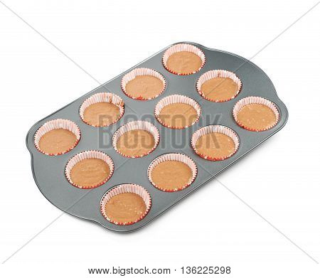 Metal muffin cupcake tray pan filled with the raw dough, composition isolated over the white background