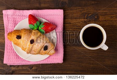 delicious golden croissants filled with strawberry marmalade and coffee. wooden table background. Top view