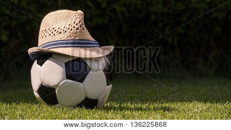 a football with a hat lying on a meadow