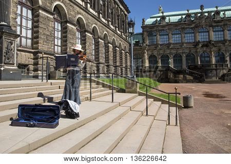 DRESDEN, GERMANY - JUNE 5, 2013:Violinist on the steps of the Dresden Art Gallery