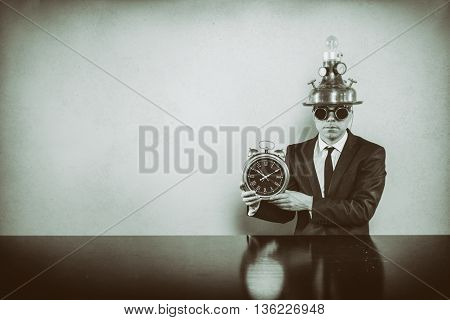 Vintage businessman sitting at office desk with clock