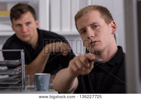Two policemen working at a police station police officer pointing with his finger