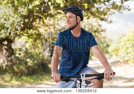 Healthy senior athlete cycling in the park and looking away. Happy fit retired man exercising while cycling in the countryside. Hppy senior man riding a mountain bike in a summer day.