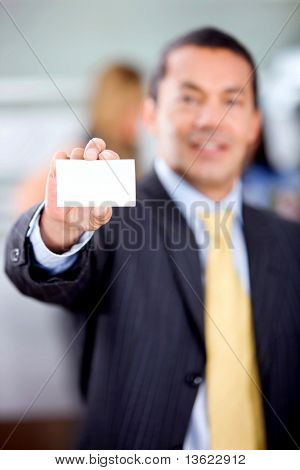 Businessman showing his business card in an office smiling