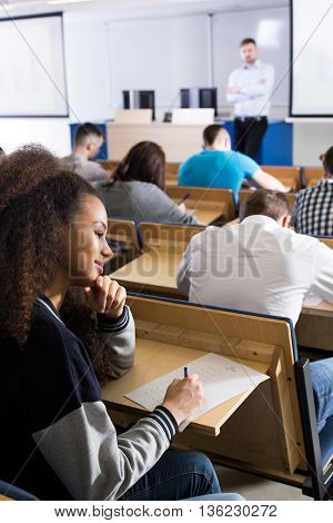 Dark-skinned female student writing on a piece of paper in a lecture room next to her friends also taking the exam